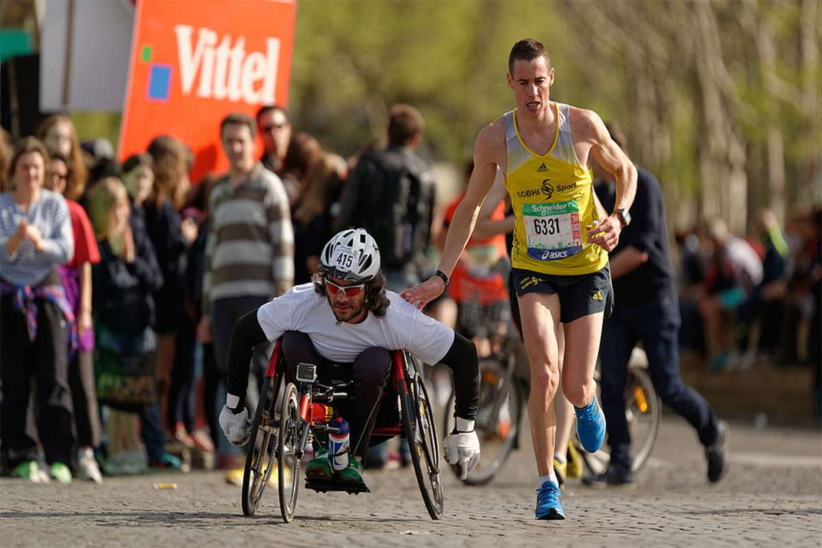 A runner gives a friendly tap on the shoulder to a wheelchair racer during the Marathon International de Paris (Paris Marathon) in 2018